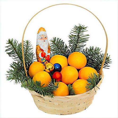 цитрусы в маленькой корзине с новогодним декором и шоколадным Дедом Морозом