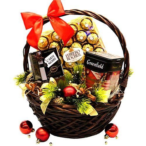 несколько коробок чая, конфеты в корзине в новогоднем оформлении