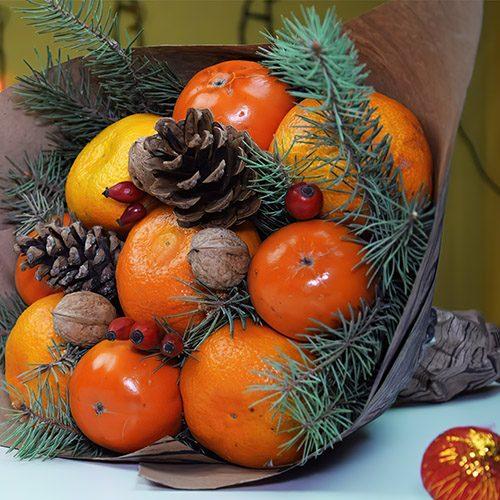 оранжевые фрукты, ветки ели, шишки и орехи